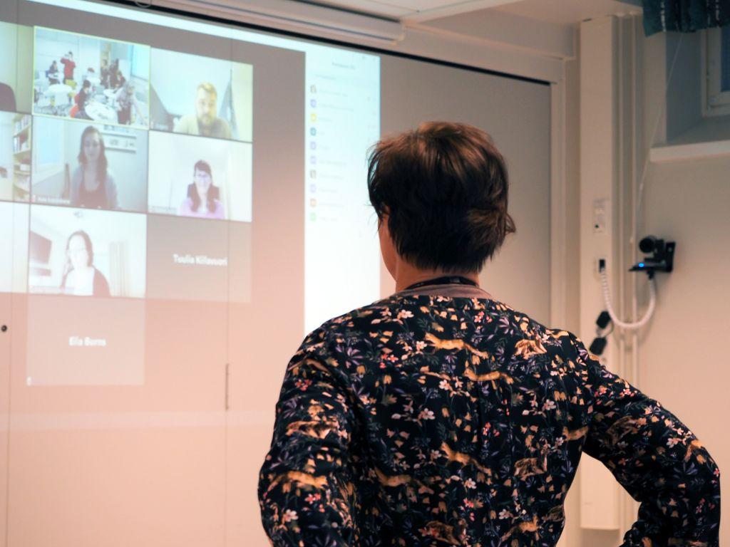 Opettaja seisoo selin kameraan ja katsoo screenillä näkyviä etäosallistujia.