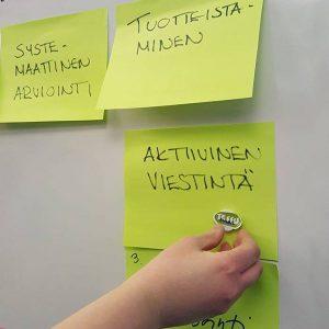 tarralappuja taululla arviointipäivässä, lapussa lukee Aktiivinen viestintä