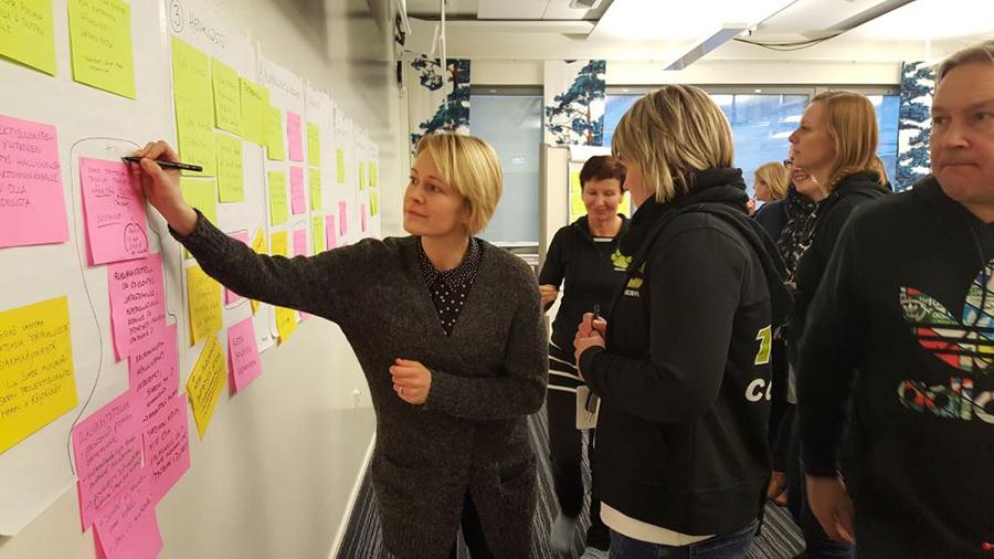 projektin työntekijöitä valkotaulun äärellä merkitsemässä tärkeimpiä kehittämiskohteita
